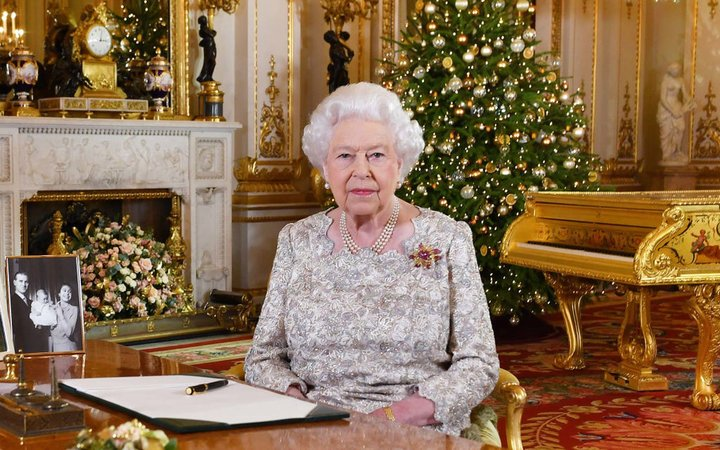 A picture released on December 24, 2018 shows Britain's Queen Elizabeth II posing for a photograph after she recorded her annual Christmas Day message, in the White Drawing Room of Buckingham Palace in central London