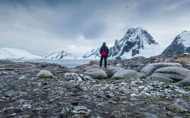 Tourist looking at the landscape in Petermann Island in the Antarctica peninsula