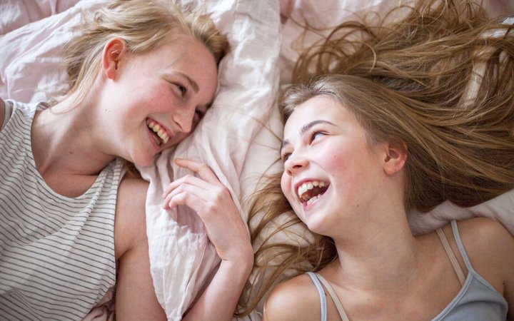 Laughing girls on bed