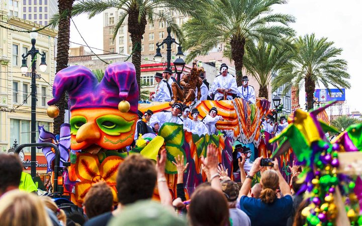 Mardi Gras parades through the streets of New Orleans. People are celebrating and welcoming locals and visitors. This is the biggest annual celebration of the city.