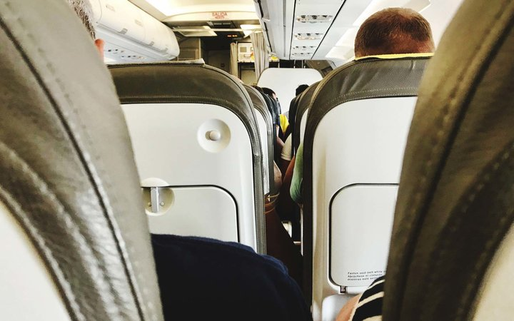 Rear View Passengers Sitting In Airplane