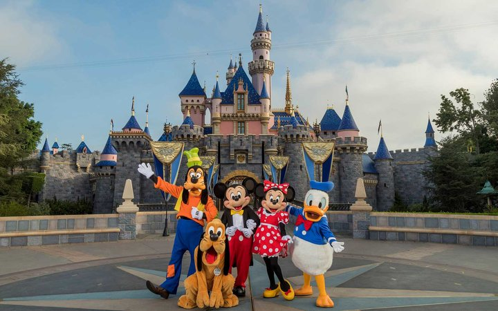 The Disney characters, Goofy, Pluto, Mickey, Minnie and Donald Duck in front of the castle at Disneyland in California