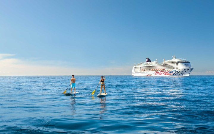 Norwegian Cruise Line ship in Hawaii waters with two people paddle boarding