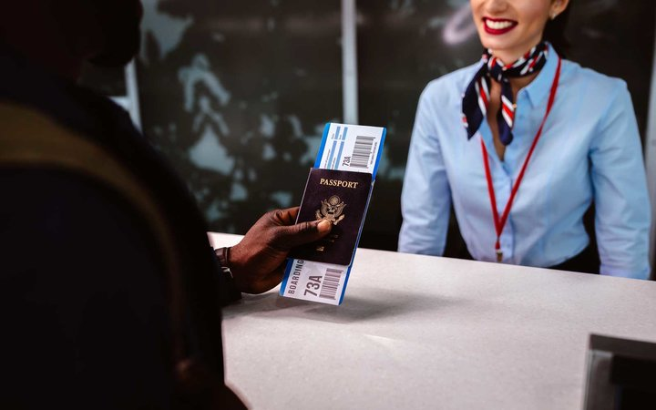 Traveler holding passport and boarding pass at airport check-in counter
