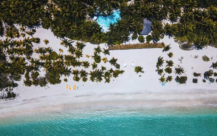 Aerial view of the beach at Kamalame Cay resort in the Bahamas, with white sand and turquoise water