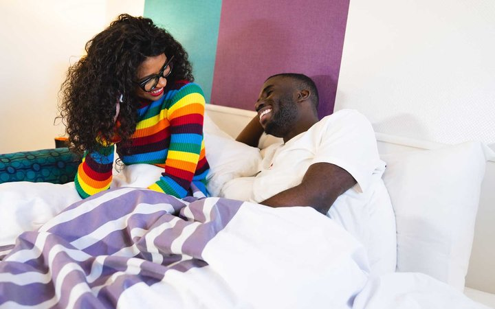 A couple cozy in bed at Hotel Zed