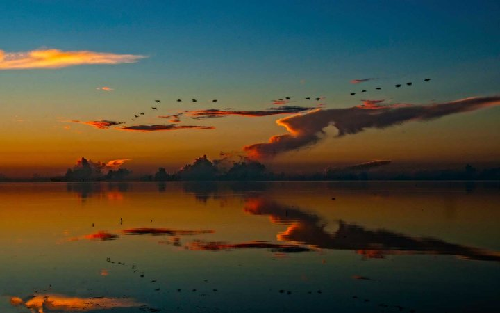 A colorful sunrise, dramatic clouds, and flight of ibis are reflected in the still waters of Biscayne Bay.