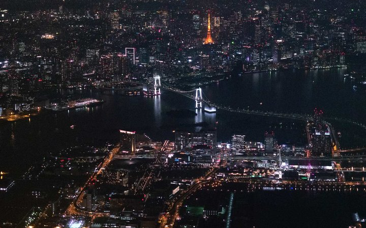 The photo was taken from commercial airplane, Tokyo Haneda International Airport (HND) to Akita Airpot (AXT). The above red-illuminated tower is Tokyo Tower and the left suspension bridge is Rainbow Bridge.