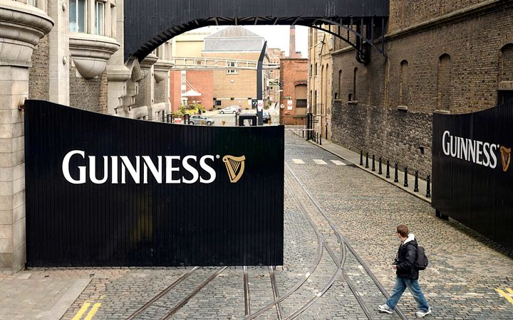 A man walking past large entrance gates to the St. James's Gate Brewery in Dublin, where Guinness has been made since 1759.