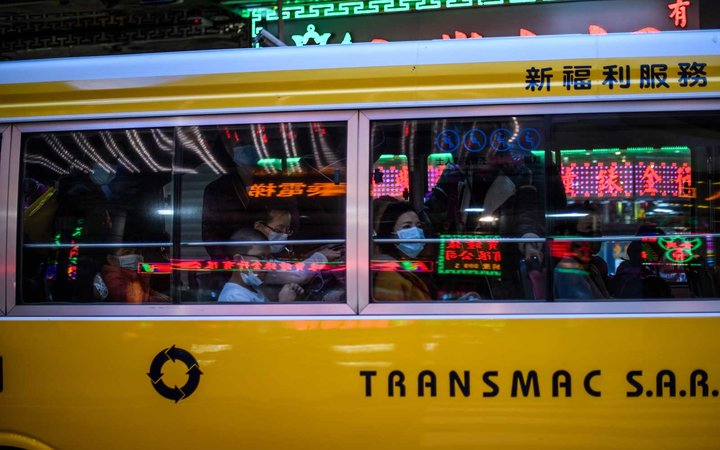 Commuters wear face masks as they travel in a bus in Macau on January 22, 2020, after the former Portuguese colony reported its first case of the new SARS-like virus that originated from Wuhan in China.