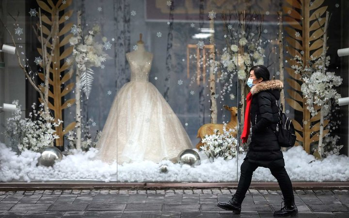 A woman wears a mask while passing in front of wedding shop on January 22, 2020 in Wuhan, Hubei province, China.