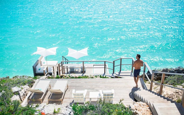 Man walking down stairs from a villa to the turquoise sea in the Turks & Caicos