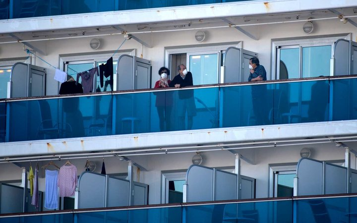 Passenger of the Diamond Princess cruise ship stand on their cabins' balconies at the Daikoku Pier Cruise Terminal in Yokohama, south of Tokyo, Japan, 13 February 2020.