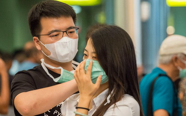 A man helping woman with medical mask