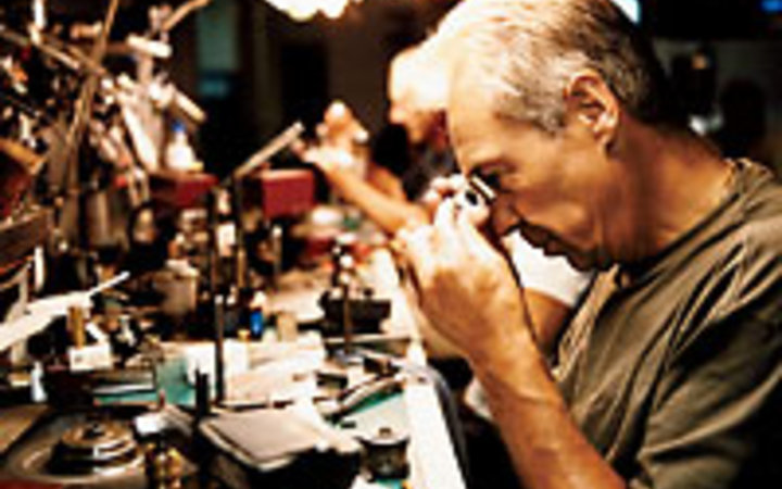 Christian Kerber A man examining a diamond for cut, clarity, and color.