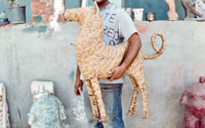 Christopher Sturman Ahmed Askalany, in his rooftp studio, wiht a sculpture made of palm leaves.