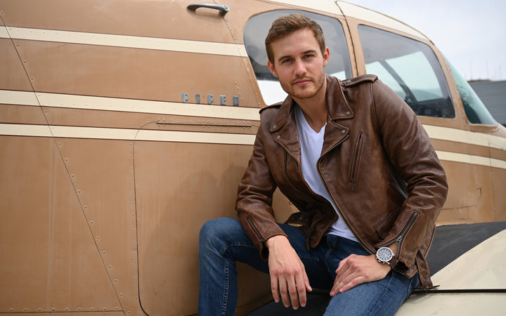 Peter Weber, Delta Pilot and The Bachelor Season 24 poses in front of a plane