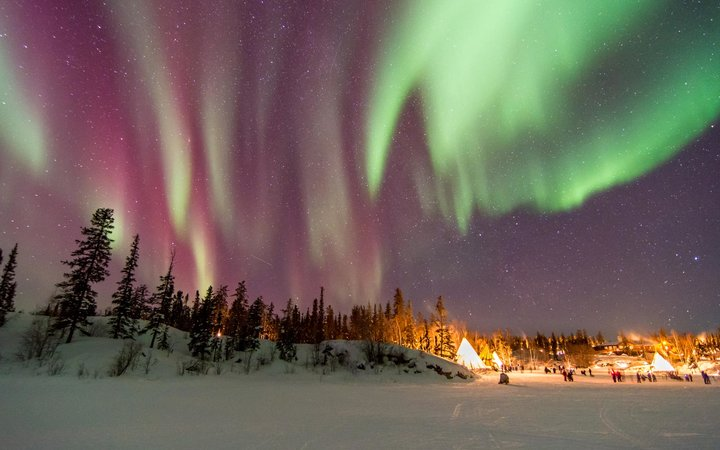 Aurora Borealis over tepees in Yellowknife, Canada