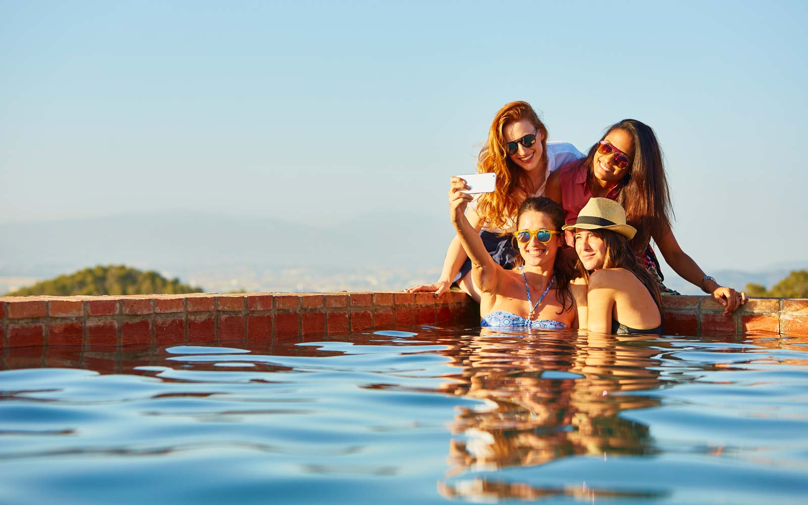 Female friends taking self portrait at pool's edge