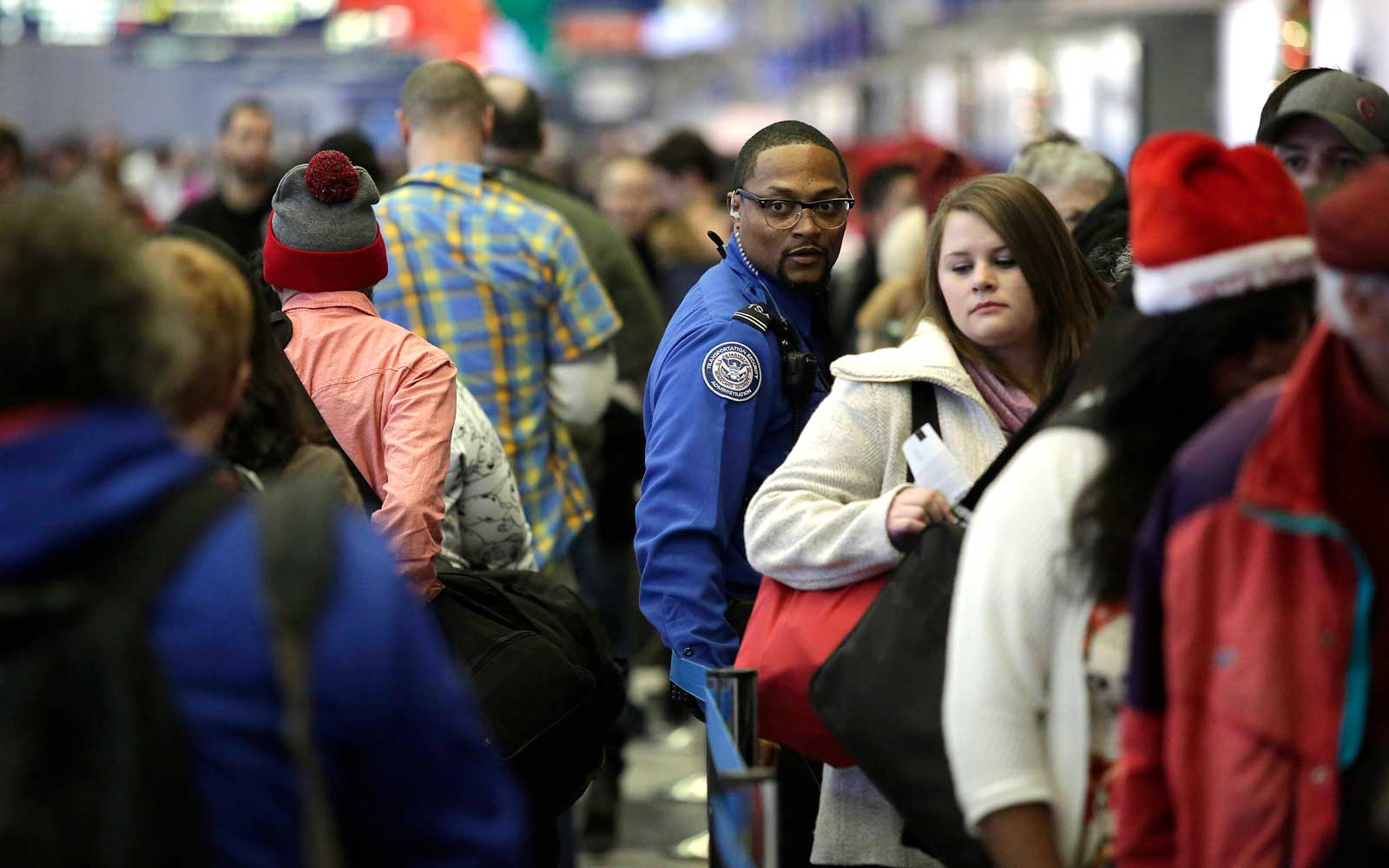 A TSA agent stands with travelers in the TSA security line at O'Hare International Airport