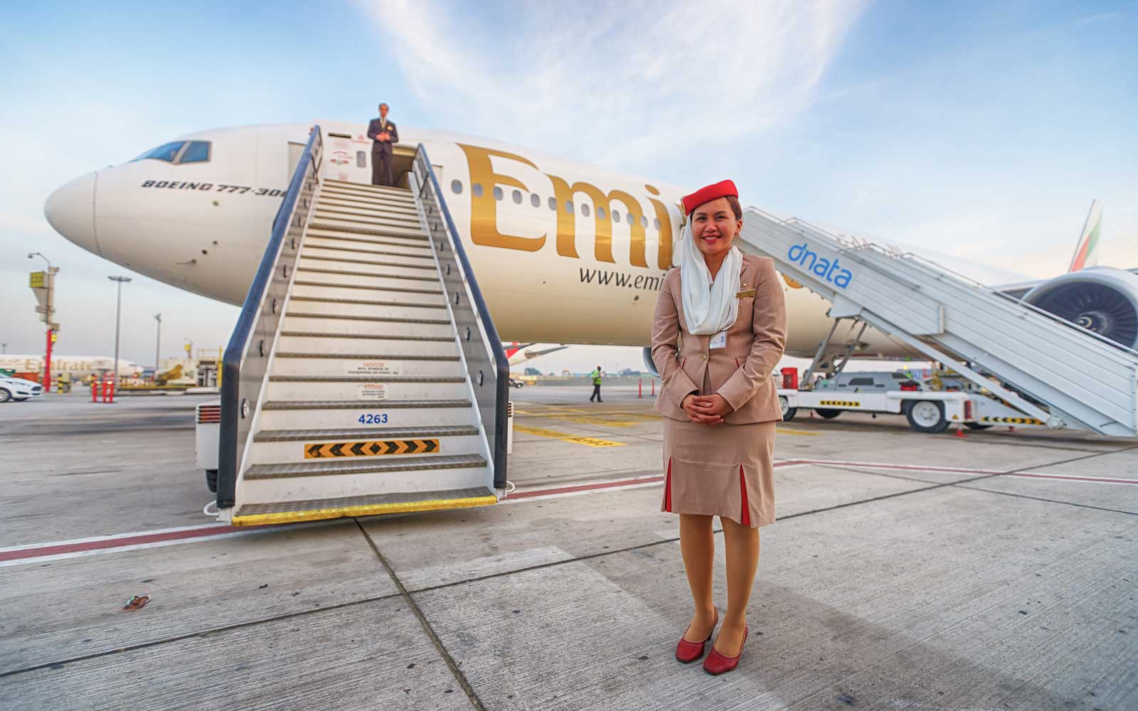 Emirates flight attendant standing outside of an airplane at the airport