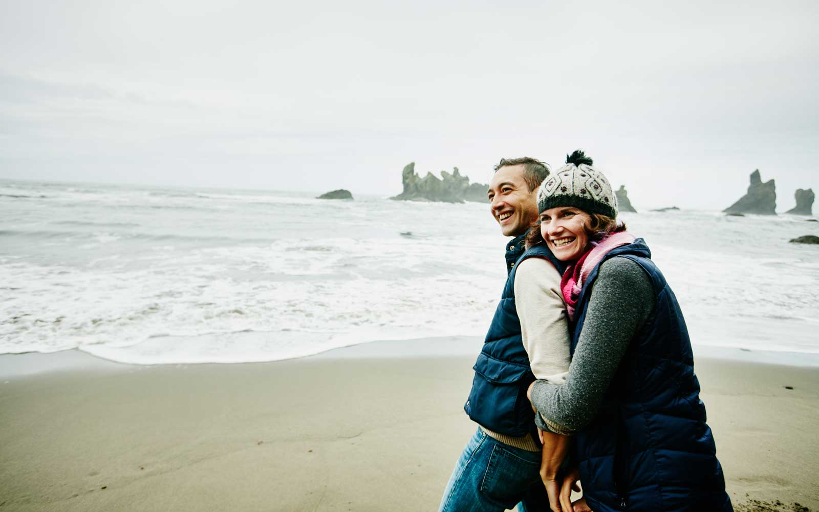 Couple enjoying time on the beach during winter