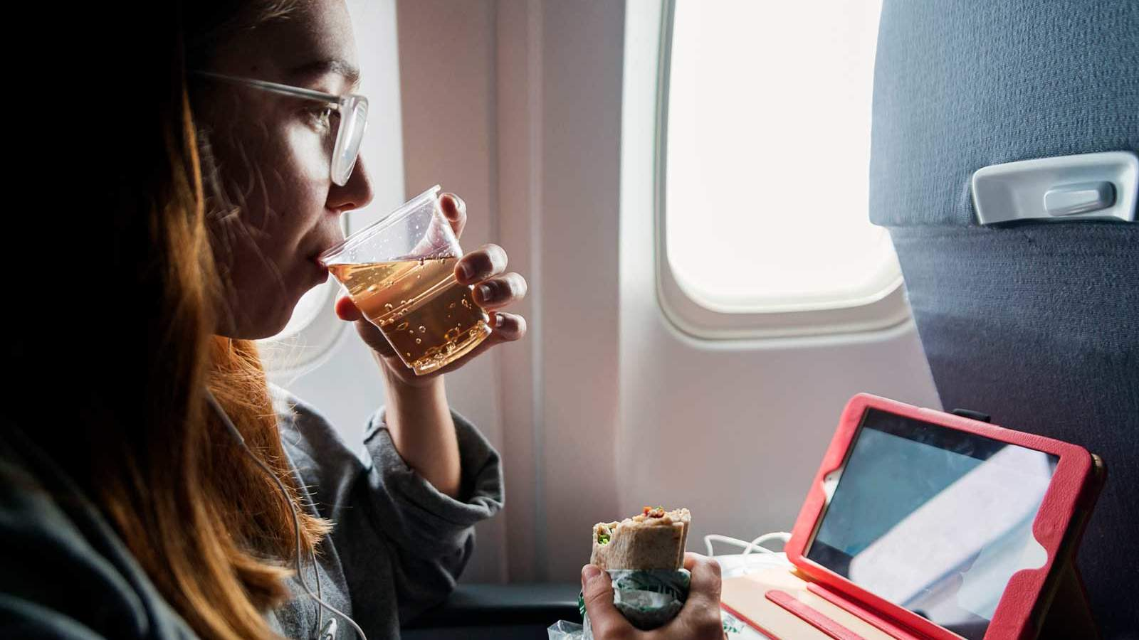 Person drinking ginger ale on an airplane