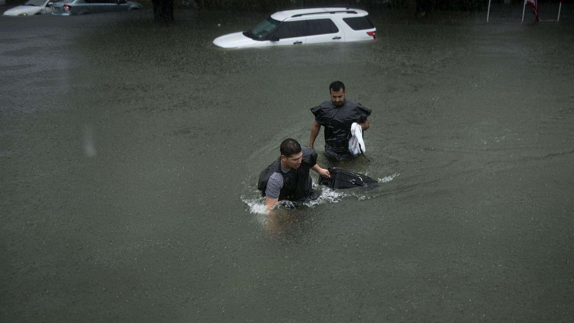 People walk through flooded streets during the aftermath of Hurricane Harvey in Houston, Texas, on Aug. 27, 2017.