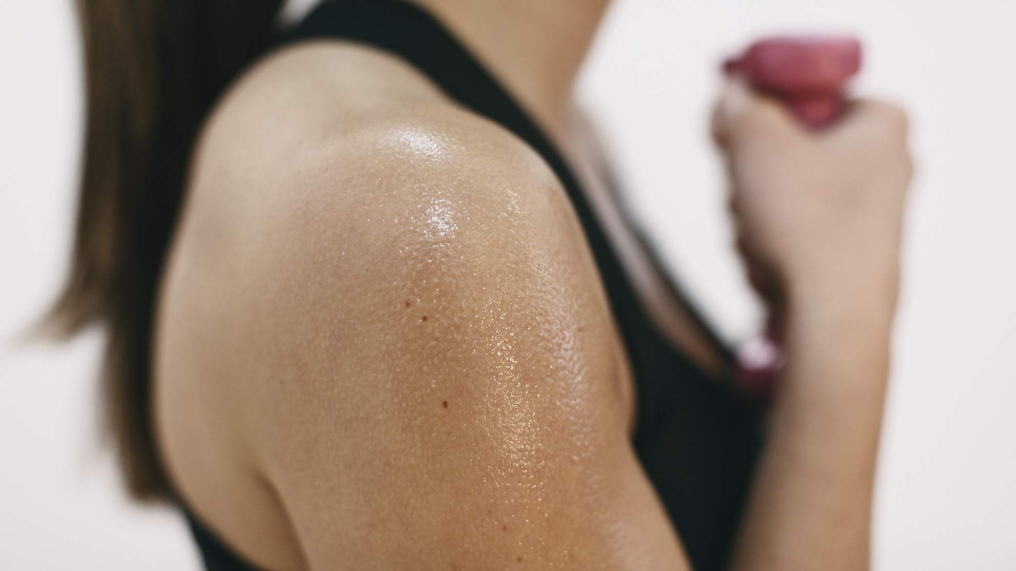 Sweaty shoulder of woman doing fitness workout TIME health stock