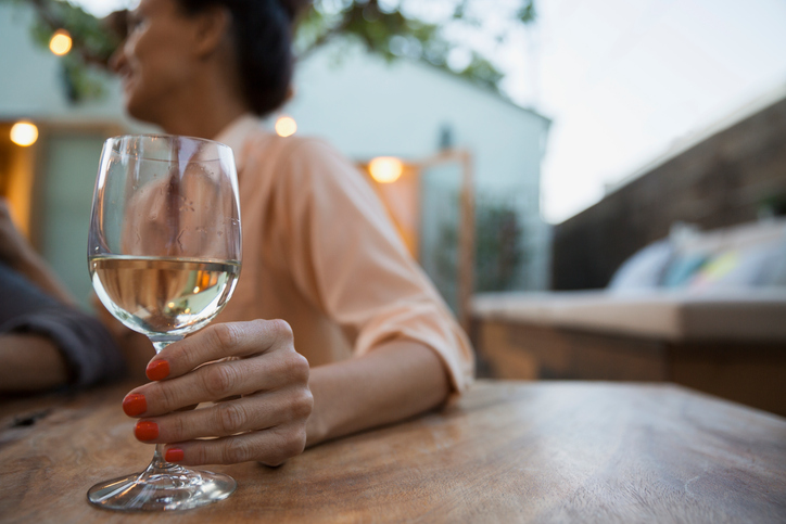 Woman drinking white wine on patio lower calorie low carb wine alcohol health