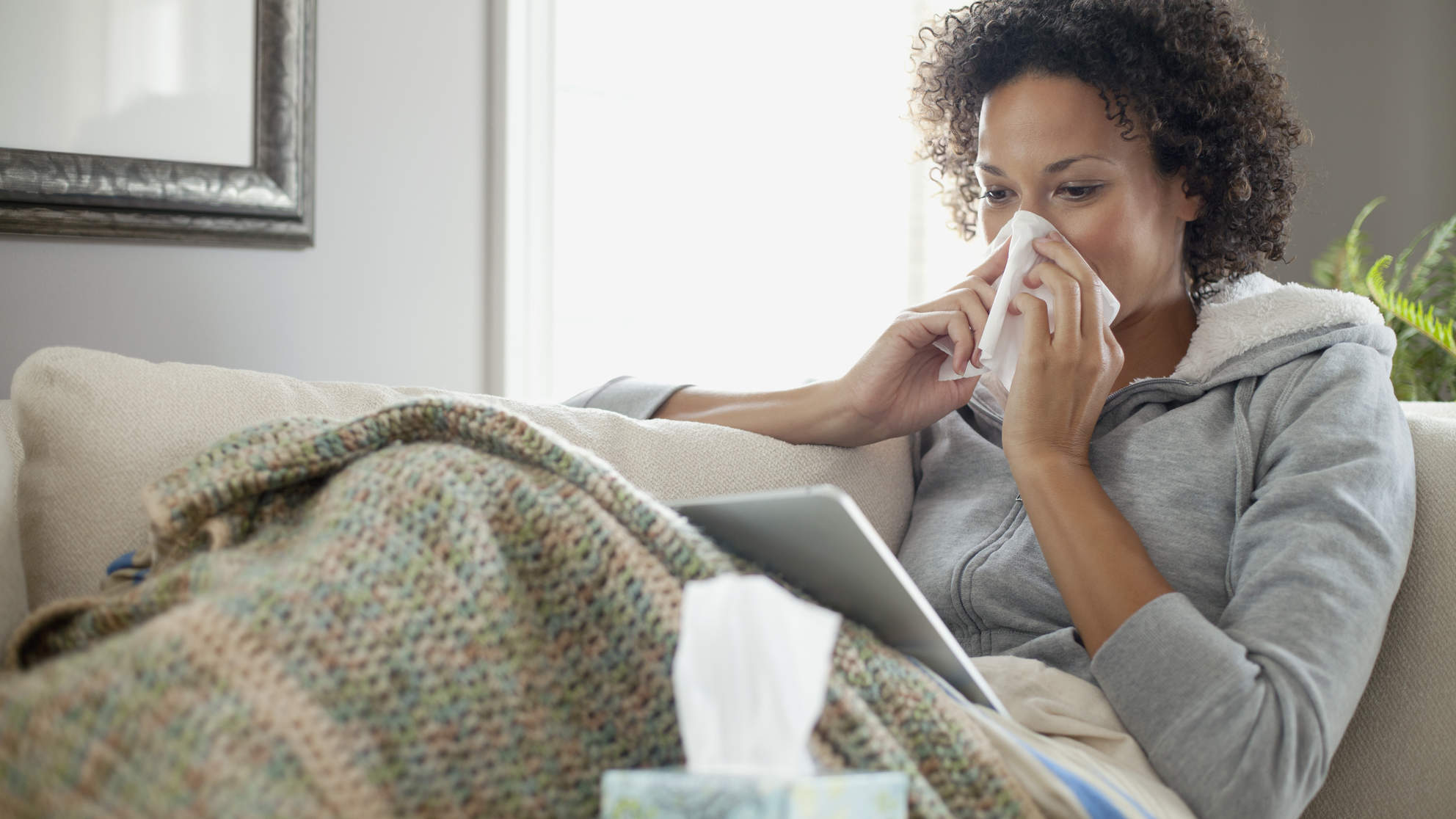 Woman nursing a cold or flu at home with stuffy nose
