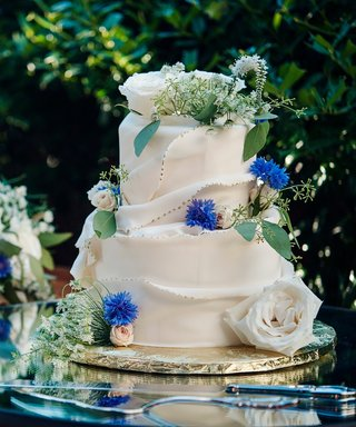 Wedding Cake Decorated With Flowers On Table