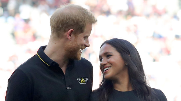 LONDON, ENGLAND - JUNE 29: Prince Harry, Duke of Sussex and Meghan, Duchess of Sussex accompany Invictus Games competitors on the field for the ceremonial first pitch before game one of the London Series between the New York Yankees and the Boston Red...