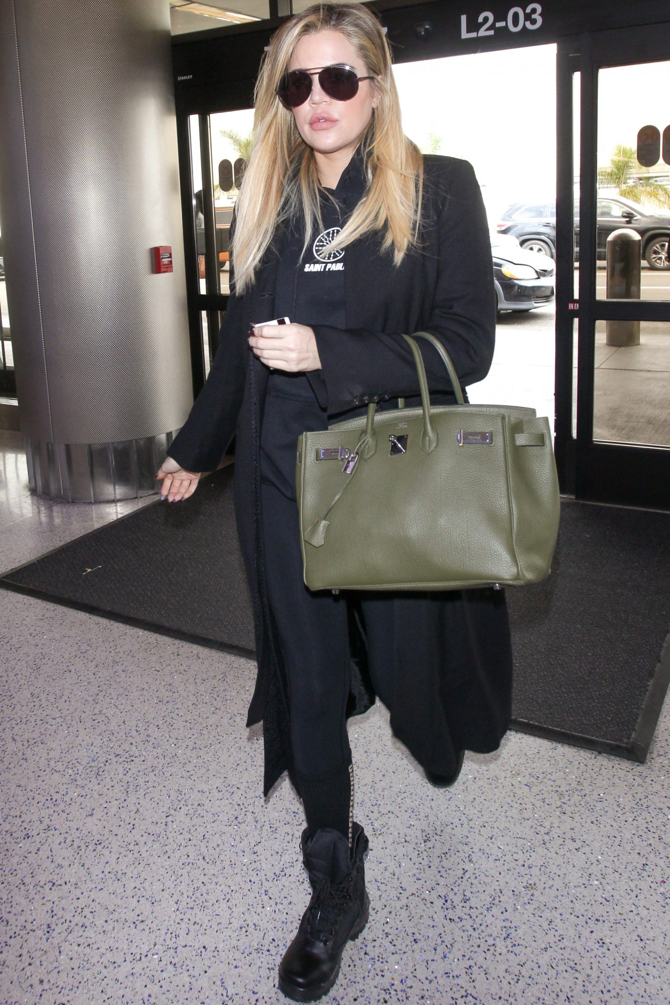 In flat black boots with a pop-of-color bag