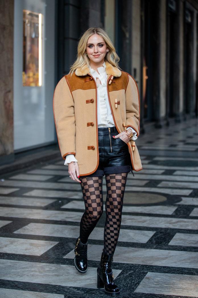leather shorts fashion trend 2020, chiara ferragni wearing leather shorts and tights at milan fashion week