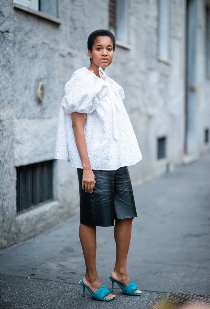 leather shorts fashion trend 2020, leather shorts and white puff-sleeve shirt outfit
