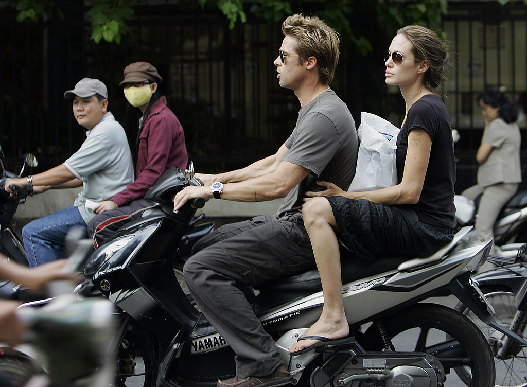 Ho Chi Minh City, VIET NAM: (FILES) Hollywood movie stars Brad Pitt (C) and his partner Angelina Jolie ride on a motorcycle on a busy street in downtown Ho Chi Minh city, 23 November 2006.  Jolie, the partner of fellow screen idol Brad Pitt, was expected to adopt a three-year-old Vietnamese boy 15 March 2007, according to the head of the Tam Binh orphanage, from where the child is.  AFP PHOTO/FILES (Photo credit should read STR/AFP/Getty Images)