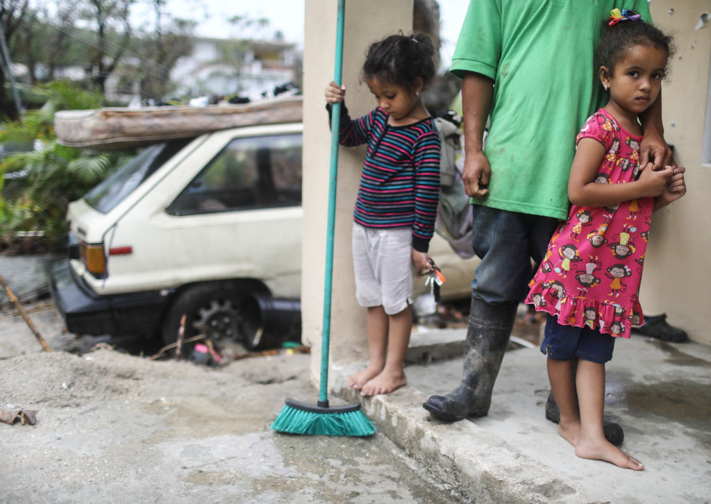 JAYUYA, PUERTO RICO - OCTOBER 09:  Young members of the Timoral family stand in front of their damaged home, with no running water or electricity, more than two weeks after Hurricane Maria hit the island, on October 9, 2017 in Jayuya, Puerto Rico. Only 15 percent of Puerto Rico's electricity has been restored. Puerto Rico experienced widespread damage including most of the electrical, gas and water grid as well as agriculture after Hurricane Maria, a category 4 hurricane, swept through.  (Photo by Mario Tama/Getty Images)
