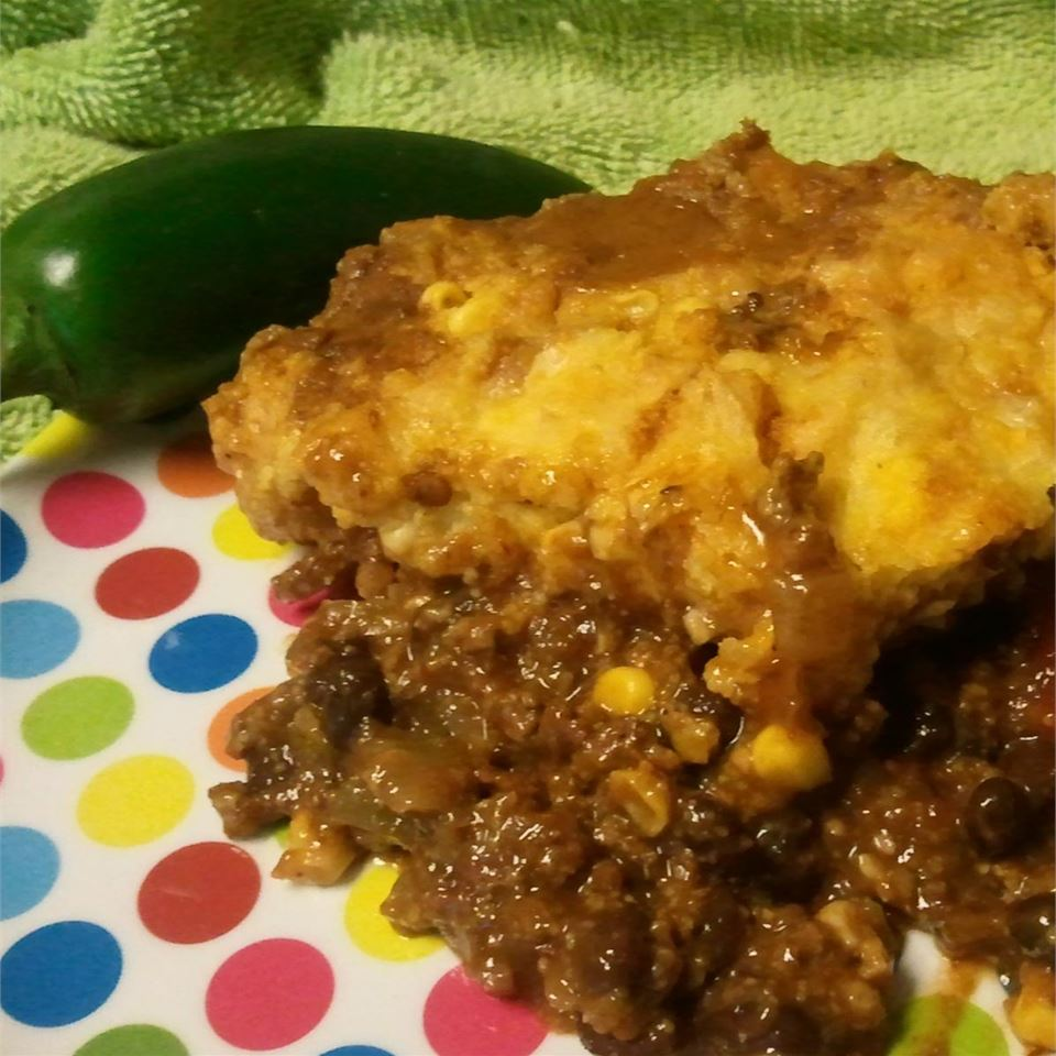 This simple recipe combines several favorite Mexican foods into a one-skillet tamale bake, featuring seasoned ground chuck and black beans covered in a cheesy cornbread topping.