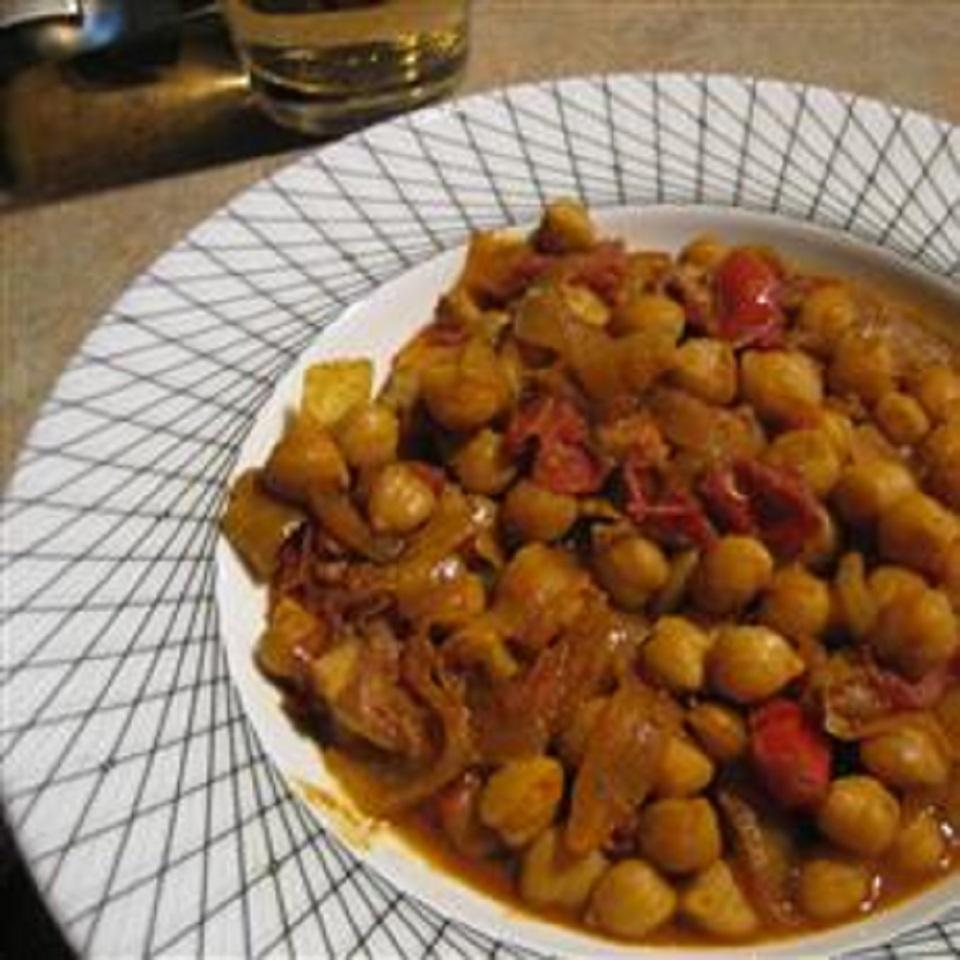 """Ready in 45 mins                           Here's a delicious traditional vegetarian Indian dish of chickpeas, onions, tomatoes, and spices. """"This is simple and great, simply great!"""" says domestic-novice. """"I doubled the tomato sauce and yogurt as well as added chicken. I, too, used canned green chilies and it was still delicious!"""""""