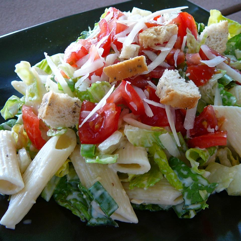 """Penne pasta mixes it up with cooked cubes of chicken, chopped fresh tomatoes, shredded romaine lettuce, Caesar salad dressing, and red wine vinegar. Garnish with croutons and Parmesan curls, if you like. """"This was so delicious!"""" says Lindy505. """"Easy to put together, and if you enjoy Caesar salad, you're sure to love this recipe."""""""