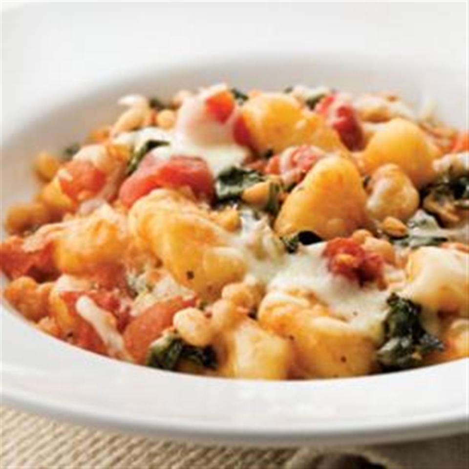 """""""In this one-skillet supper, we toss dark leafy greens, diced tomatoes, and white beans with gnocchi and top it all with mozzarella,"""" says Breana Lai."""
