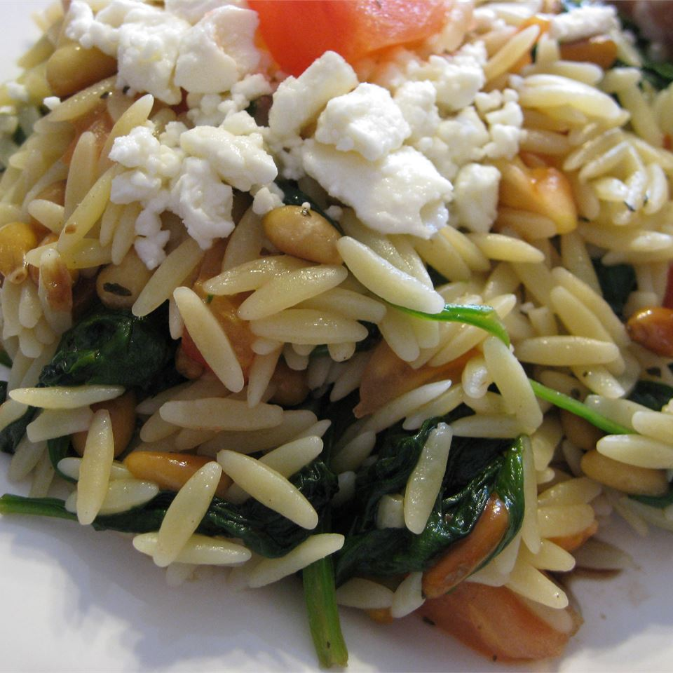 Sautéed spinach, garlic, basil, and toasted pine nuts are served on top of tender orzo pasta. Top with a drizzle of balsamic vinegar, chopped tomatoes, and crumbled feta cheese for fabulous flavor in every bite.