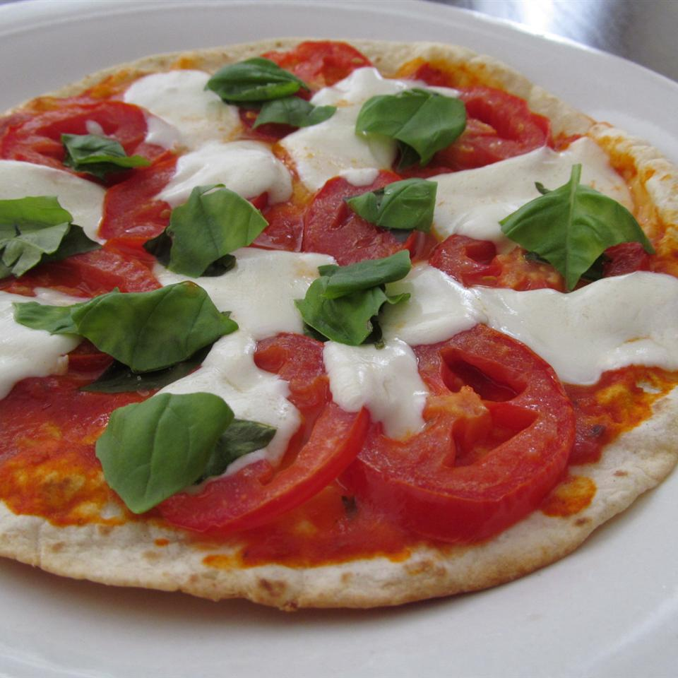 """""""Basil pesto, fresh mozzarella, roasted tomatoes and fresh basil leaves top a crispy flatbread for individual pizzas,"""" says Tricia L. """"Don't worry if you don't have time for the dough to rise to make the flatbread -- this uses store-bought flour tortillas as an alternate base. Quick, easy and delicious!"""""""