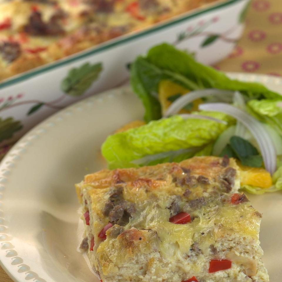 "The ""strata"" in this classic casserole are layers of bread, cheese and sausage baked in an egg-rich pudding."