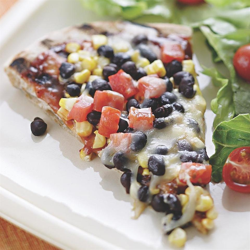 The secret to a grilled pizza is having all your ingredients ready to go before you head out to the grill. Make it a meal: Toss the extra black beans, diced tomato and some avocado with prewashed salad greens and a tangy vinaigrette and dinner is on the table in no time. Source: EatingWell Magazine, June/July 2006