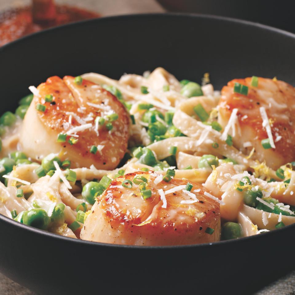 This rich pasta dish is full of sweet seared scallops and plump peas. Low-fat milk and flour thicken the sauce, giving it creamy texture without the extra calories and fat found in traditional cream sauces. Serve with a small Caesar salad on the side.