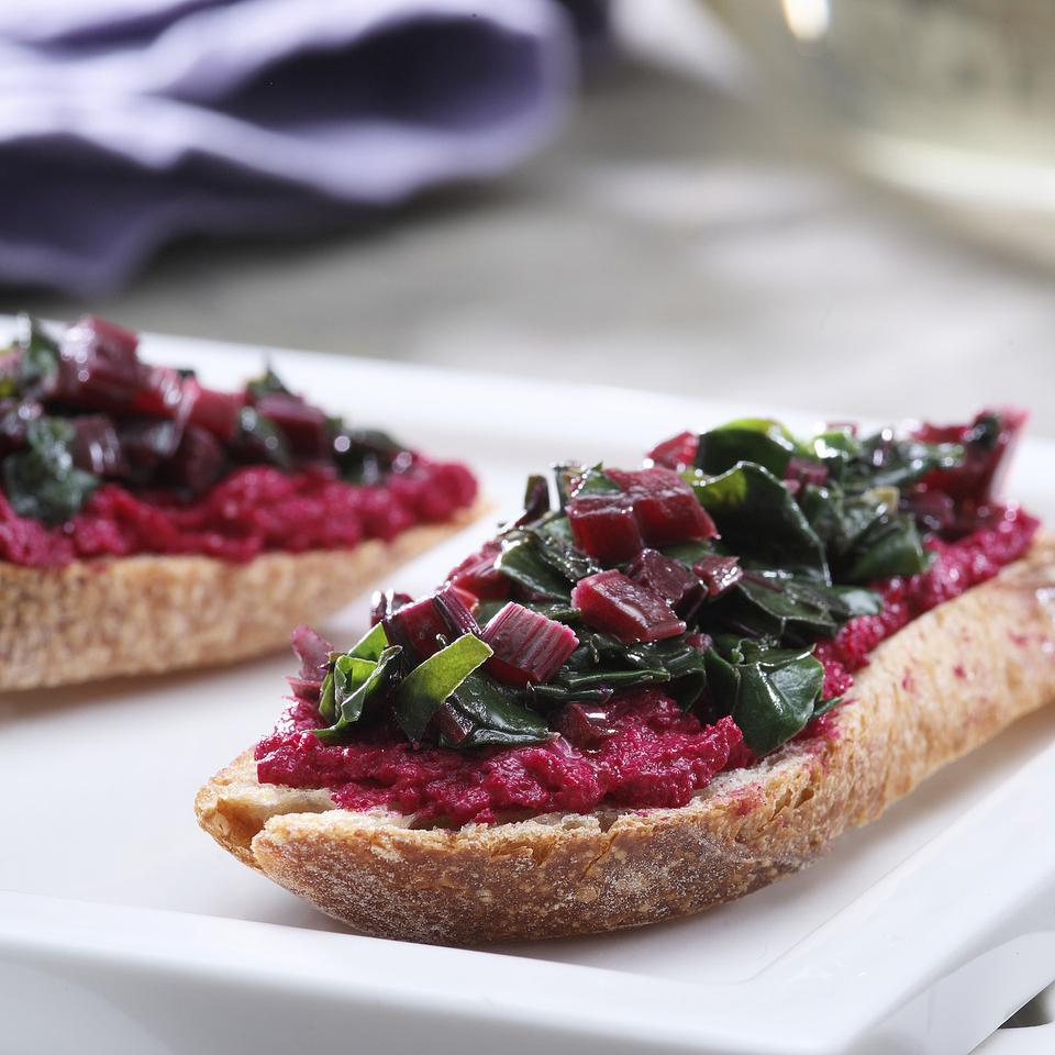 The entire beet plant—roots, stems and greens—can be used in this stunning appetizer. The beets are roasted then pureed with goat cheese for a creamy ruby-red spread. The greens and stems are sautéed with olive oil and garlic for the topping.