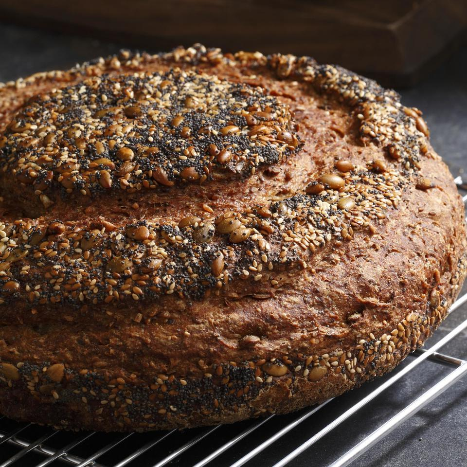 Not only is this seeded loaf high in fiber, but the blend of seeds and grains lends it a wonderfully nutty flavor, aroma and texture. A heavy container with a tight-fitting lid works best, as the steam trapped inside the pot helps crisp the crust of the boule. Keep in mind that in a very wide-bottomed pot the loaf will spread out and be fairly flat; in a taller, narrower one it will be thicker and have more height (but may take slightly longer to bake). Source: EatingWell Magazine, January/February 2009