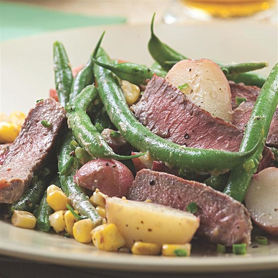 The classic combination of steak and potatoes gets a summer makeover with the addition of fresh grilled corn and green beans. Reserve some of the tangy horseradish dressing if you like and toss it with lettuce as a bed for the steak salad. Serve with a glass of cold pilsner.Source: EatingWell Magazine, July/August 2010